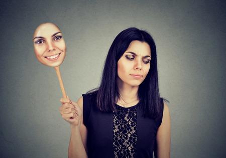 Jonge vrouw met het droevige uitdrukking nemen van een masker die opgewektheid uitdrukken Stockfoto