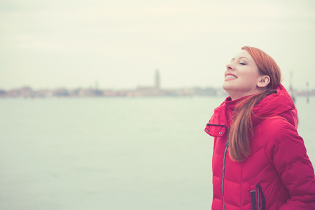 Side profile woman smiling looking up to sky enjoying freedom on a background city of Venice Italy . Positive emotion face expression life perception photo