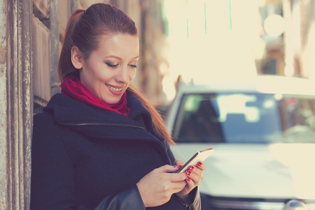 Woman smiling holding a mobile phone standing outdoors next to her new car texting. photo