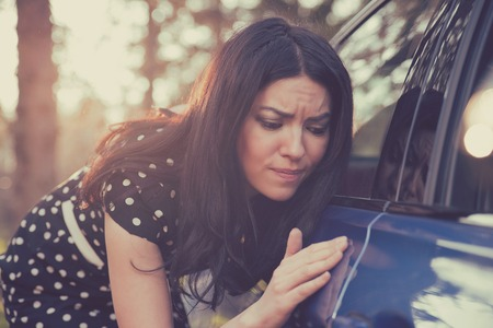 Young worried funny looking woman obsessing about cleanliness of her new car. Automobile care and protection concept Stock Photo