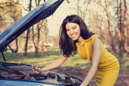 manage transportation: Portrait of a happy woman holding a wrench confidently with her broken down car on a rural park forest background