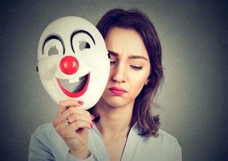 회색 벽 배경에 고립 행복 광대 마스크를 이륙하는 세로 슬픈 여자. 인간의 감정의 감정 스톡 콘텐츠