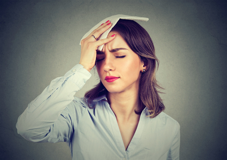 young woman wipes sweat from her forehead with a handkerchief