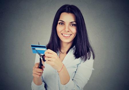 Gelukkige vrouw snijden in de helft van haar creditcard met een schaar geïsoleerd op een grijze achtergrond