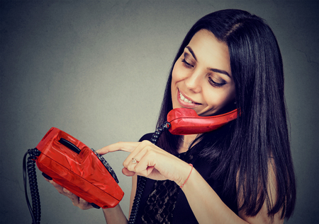 Young woman on the phone dialing the number