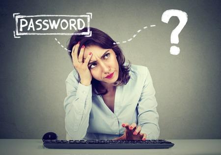 Verzweifelte junge Frau versucht, sich in ihren Computer einloggen Passwort vergessen Standard-Bild