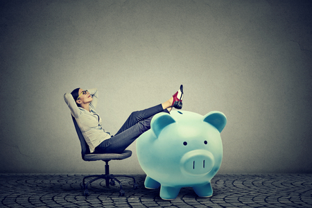 young businesswoman with big piggy bank relaxing sitting on chair photo
