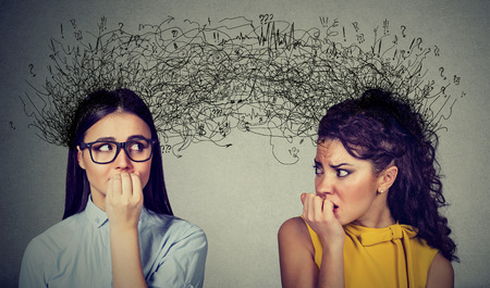 Side profile of two preoccupied anxious women looking at each other exchanging with many thoughts Archivio Fotografico