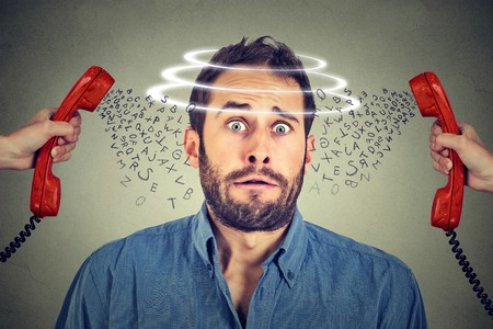 Head is spinning. Astonished scared man stressed and nervous from too many angry calls on the phone Archivio Fotografico