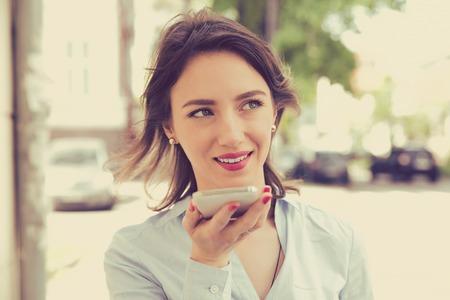Mujer que usa una función de reconocimiento de voz de teléfono inteligente en línea caminando en una calle de la ciudad en un día de verano Foto de archivo