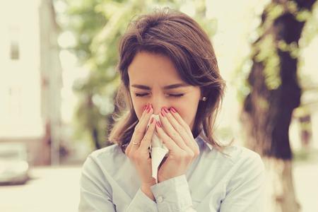 Vrouw met allergiesymptomen die neus blazen Stockfoto