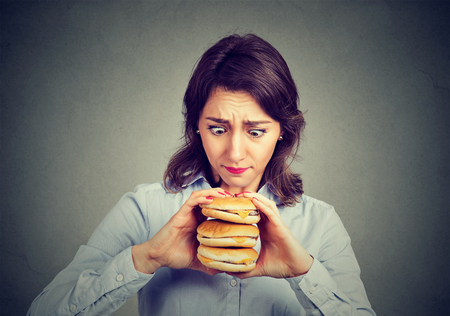 Woman eating craving a tasty triple burger