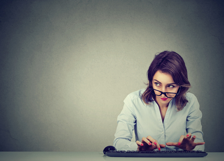 Woman typing on the keyboard wondering what to reply Stock Photo