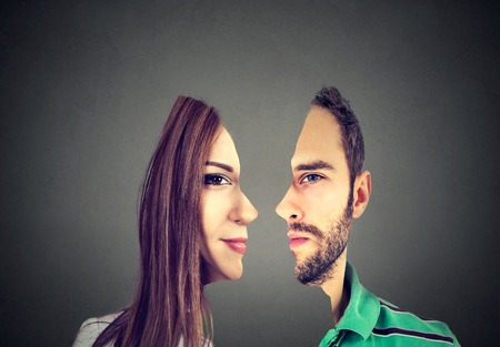 surrealistic portrait front with cut out profile of a young man and woman isolated on grey wall background