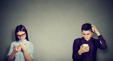 Perplexed young man and woman looking at mobile phone Stock Photo