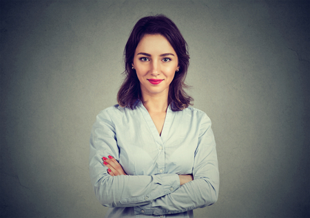 careerist: Portrait of young beautiful business woman on gray wall background