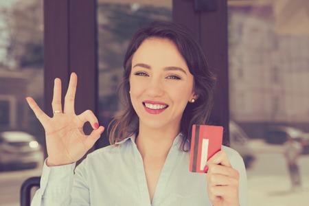 Mujer dentuda de la sonrisa que celebra mostrar la tarjeta de crédito cerca del centro comercial de la tienda de la oficina al aire libre. Pago por concepto de adicción a las compras con tarjeta de crédito Foto de archivo