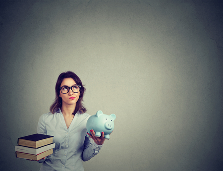 Student loan concept. Young woman with pile of books and piggy bank full of debt rethinking future career path Foto de archivo