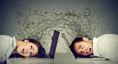 Beklemtoonde zakenvrouw en man rustend hoofd op laptop zittend aan tafel gefrustreerd met elkaar uitwisselen met rommel van negatieve gedachten en emoties. Distant relatie concept