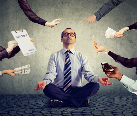 Mature business man is meditating to relieve stress of busy corporate life Фото со стока