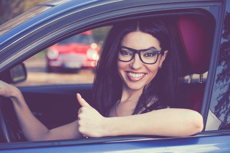 Happy woman sitting inside her new car showing thumbs up
