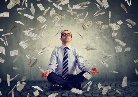Business man meditating under money rain