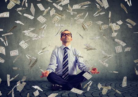 Business man meditating under money rain