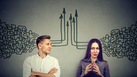 Side profile of a young man and woman looking at each other getting their thoughts together isolated on gray wall background Standard-Bild