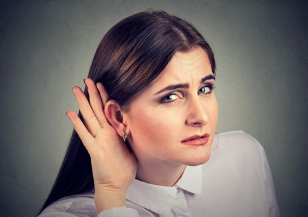 Woman with a hearing loss cupping her hand behind ear with her head turned towards camera to try and amplify available sound