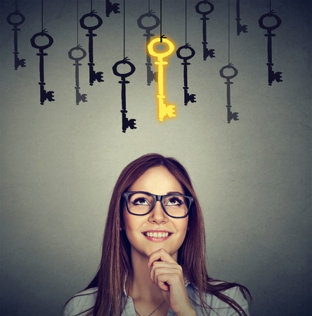 Beautiful thoughtful woman looking upSmiling woman looking up at vintage golden key to success among many others hanging. Concept of business aspirations, achievement Stock Photo