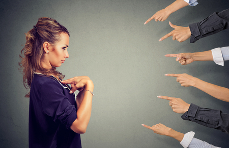 Blaming you. Anxious angry woman judged by different people pointing fingers hands at her. Negative human emotions face expression feeling Stock Photo