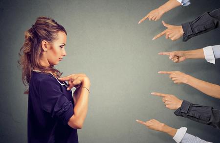 Dich beschuldigen. Ängstliche böse Frau, die von verschiedenen Leuten beurteilt wird, die Finger auf sie zeigen. Negative menschliche Gefühle stehen dem Ausdrucksgefühl gegenüber Standard-Bild