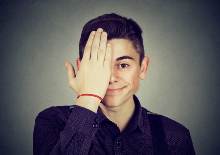 Happy young man with funny expression and hand over half face