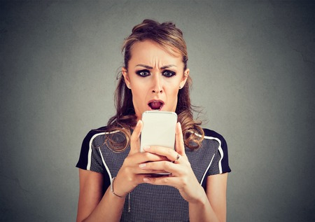 Closeup portrait funny shocked scared woman looking at phone seeing bad news photos message with disgusting emotion on face isolated on gray background.