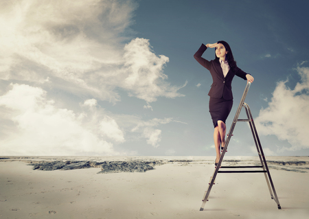 Jeune femme d & # 39 ; affaires sur une échelle en détournant les yeux dans un désert Banque d'images - 86585665