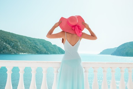 Europe Greece travel vacation. Woman looking at sea view. Elegant young lady living fancy jetset lifestyle wearing dress on holidays. Amazing view of seaside and islands