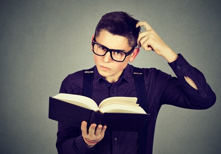 Confused young man in glasses perplexed after reading a book  Stock Photo