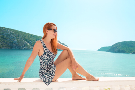 Europe Greece travel vacation. Woman looking at sea view. Young lady living fancy jetset lifestyle wearing dress on holidays. Amazing view of seaside and islands