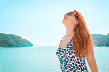 Woman smiling taking deep breath enjoying freedom and good weather by the sea. Positive human emotions, face expression feeling life perception concept.