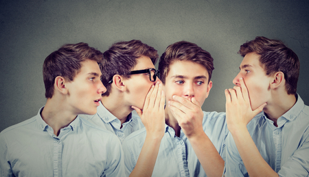 Three young men whispering each other and to shocked astonished guy in the ear. Word of mouth. 版權商用圖片