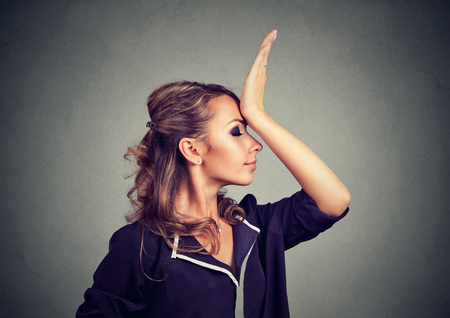 shortsighted: Regrets wrong doing. Sad woman, slapping hand on head having duh moment isolated on gray background. Negative human emotion feeling, body language