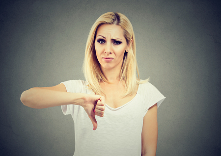 Woman giving thumb down gesture looking with negative expression and disapproval isolated on gray background