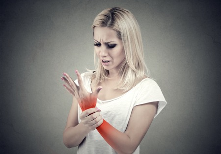 Woman holding her painful wrist isolated on gray wall background. Sprain pain location indicated by red spot.