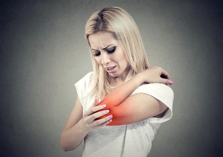 Droevige vrouw met gezamenlijke ontsteking. De elleboog van de vrouw. Arm pijn en verwonding concept.