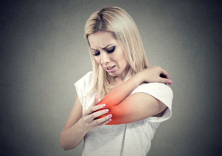 Sad woman with joint inflammation. Female's elbow. Arm pain and injury concept.