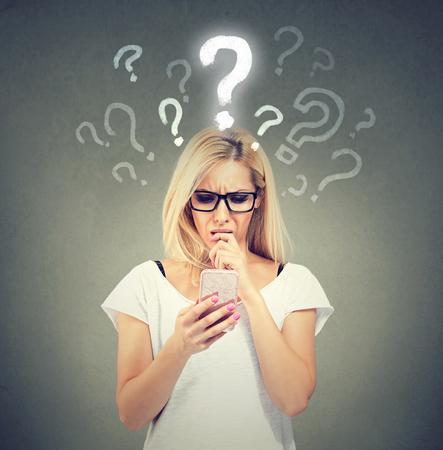 오해와 먼 전화. 화가 혼란 스 러 워 여자 이야기 또는 문자 메시지 휴대 전화 회색 배경에 고립 된 많은 질문이있다. 스톡 콘텐츠