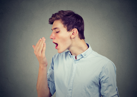 Young man checking his breath with hand. Stockfoto