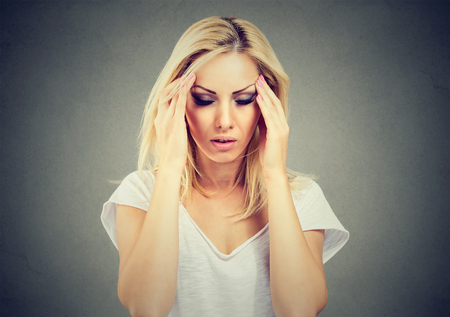 Closeup portrait sad young beautiful woman with stressed face expression looking down Standard-Bild
