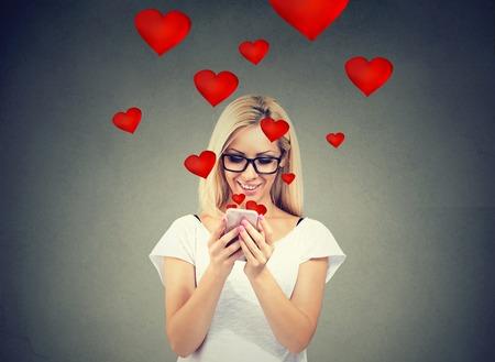 Mooie vrouw die het bericht van de liefdetekst op mobiele telefoon met rode harten verzenden die vanaf het scherm vliegen die op grijze achtergrond wordt geïsoleerd.