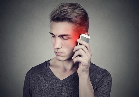 Homem no celular com dor de cabeça. Indivíduo infeliz virado que fala em um telefone isolado no fundo cinzento da parede. Emoção humana negativa enfrentar expressão sentimento reação. Foto de archivo